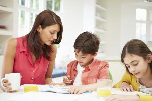 Governess Helping Children With Homework